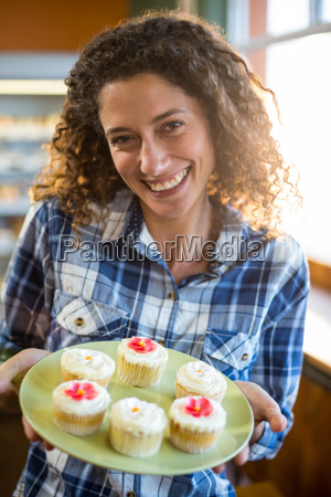 smiling woman holding plate of cup