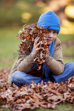 portrait of boy holding autumn leaves