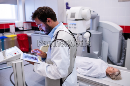doctor using digital tablet and patient
