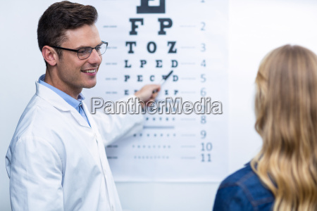 optometrist taking eye test of female