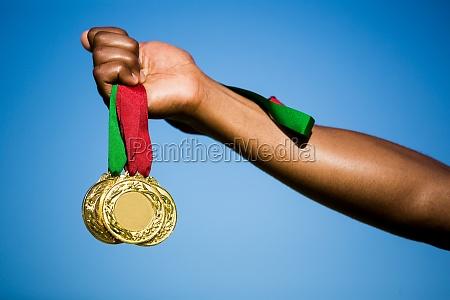 athlet hand seine goldmedaillen zeigt