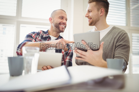 happy businessman with colleague using digital