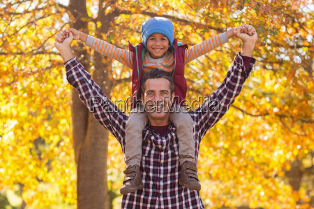 happy father carrying son on shoulder