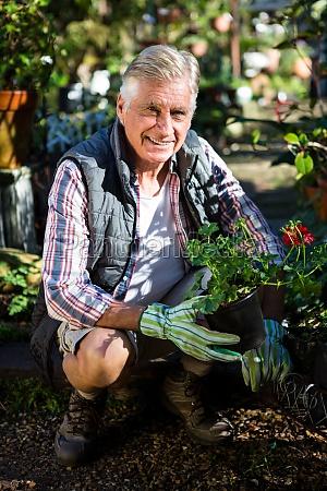 portrait of happy gardener crouching with