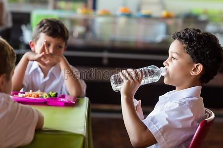 schuljunge trinkwasser aus flasche