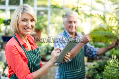 woman using digital tablet while man