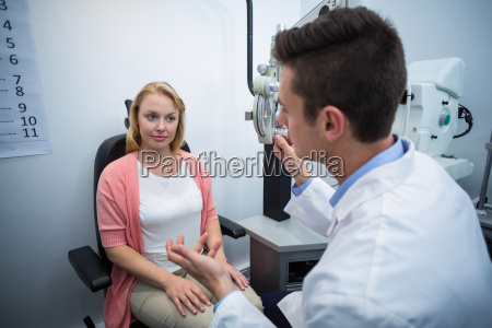 optometrist assisting female patient