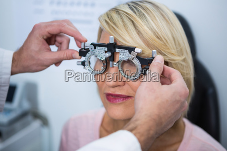 optometrist examining female patient with messbrille