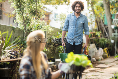 gardener working while female coworker holding