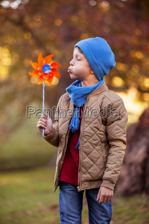 boy blowing pinwheel at park