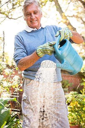 happy gardener watering plants at garden