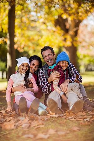 glueckliche familie sitzt im herbst im