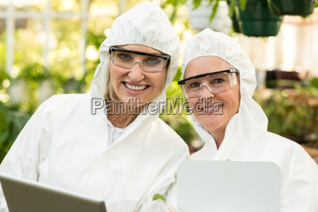 smiling female coworkers wearing clean suit