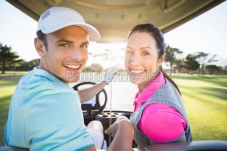 nette golfspielerpaare die im golfbuggy sitzen