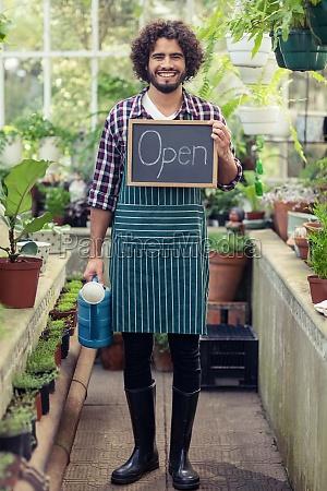 male gardener holding open sign placard