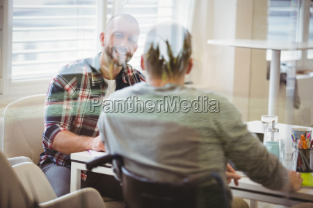 handicap businessman discussing with colleague in