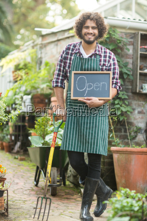 male gardener with open sign holding