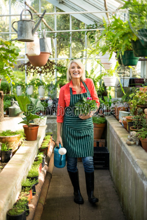 gardener with potted plant and watering