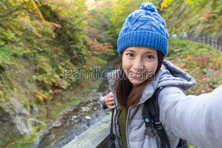 woman taking selfie by holding digital