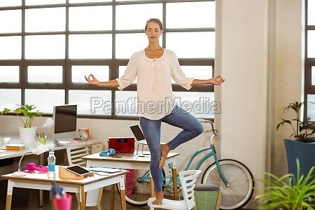 weiblicher geschaeftsmann der yoga durchfuehrt