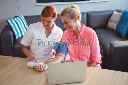 nurse measuring the blood pressure of