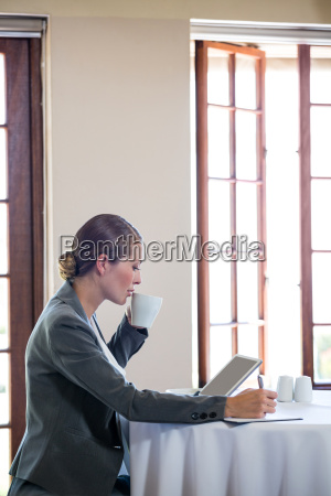 woman working and drinking a coffee