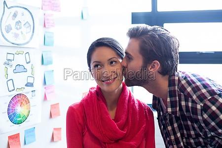 mann kuesst weibliche kollegin im kreativbuero