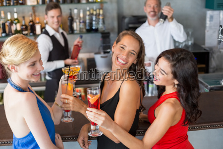 happy female friends holding glass of