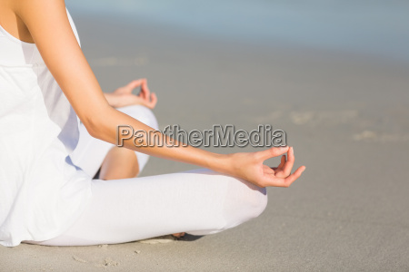 mid section of woman performing yoga