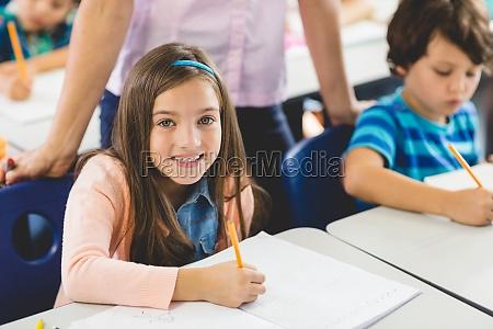 schulmaedchen macht hausaufgaben im klassenzimmer