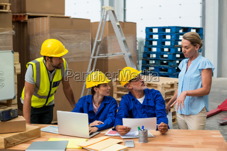 warehouse worker listening to their manager