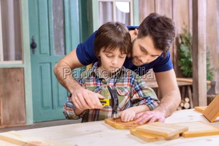 smiling father teaching concentrated son to