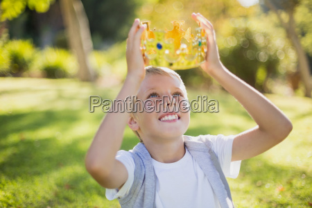 young boy holding a crown