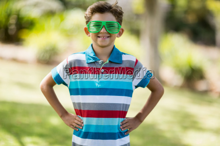 young boy in shutter shades standing