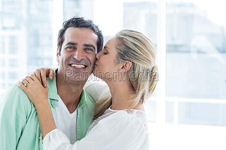 mid adult woman kissing man at