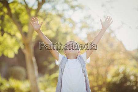 boy standing with arms outstretched in
