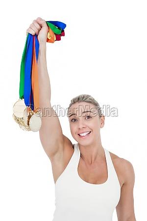 glueckliche sportlerin haelt medaillen