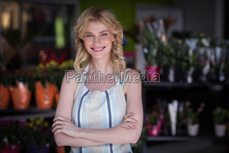 happy female florist standing with arms