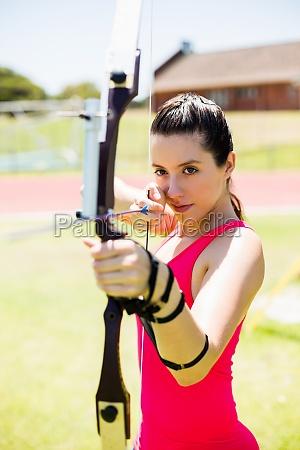 weiblicher athlet ueben bogenschiessen