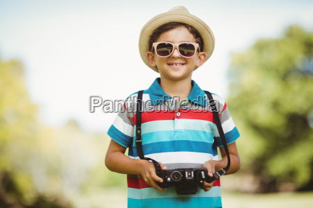 young boy in sunglasses holding a