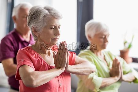 senioren machen yoga mit geschlossenen augen
