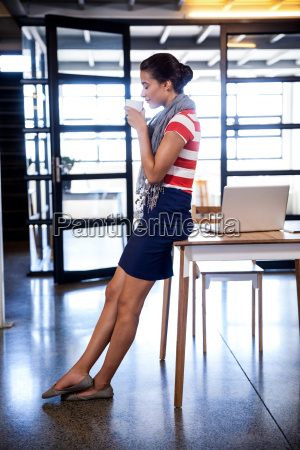 businesswoman standing and drinking a coffee