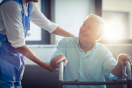 aerztin hilft senior mann mit walker