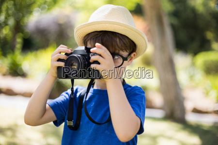 young boy clicking a photograph from