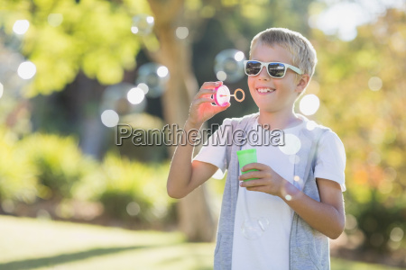 young boy blowing bubbles through bubble