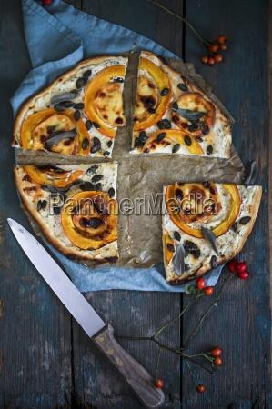 kuerbis pizza mit kuerbiskernen in viertel