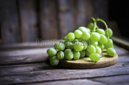 gruene trauben auf einer rustikalen holzoberflaeche