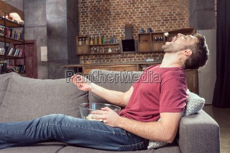 man eating popcorn while watching movie