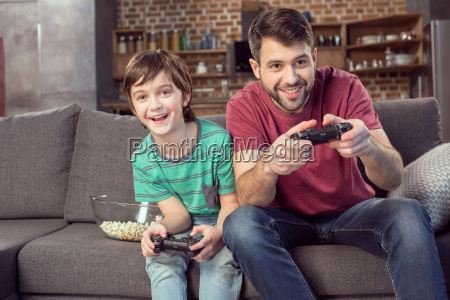 smiling father and son playing video