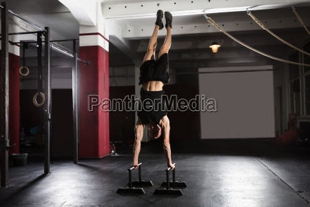 man doing handstand on parallel bar